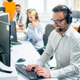 Young male technical support dispatcher with headset talking with customer in call center